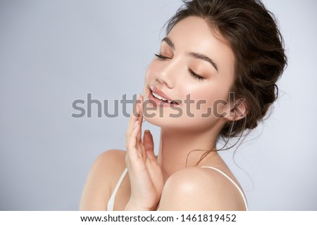 young and happy girl with light make-up and closed eyes touching her chin and smiling, shiny mua with highlighter and pinky lips Royalty-Free Stock Photo #1461819452