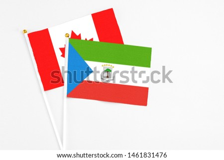 Equatorial Guinea and Canada stick flags on white background. High quality fabric, miniature national flag. Peaceful global concept.White floor for copy space. #1461831476