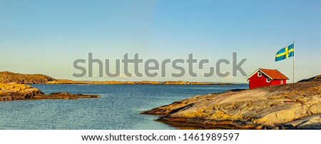Red house in Sweden at the skerry coast with flag #1461989597