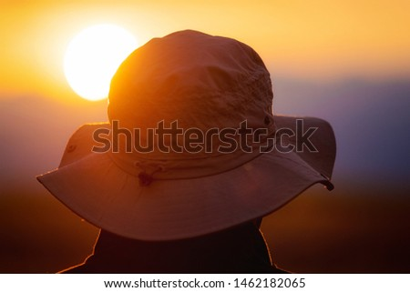 Back view of a man with explorer hat watching scenic sunset. Concept for travel exploration and discovery . #1462182065