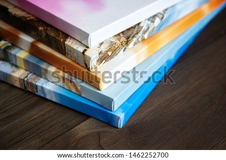 Photography canvas prints. Stacked colorful photos with gallery wrapping method of canvas stretching on stretcher bar, lateral side Royalty-Free Stock Photo #1462252700