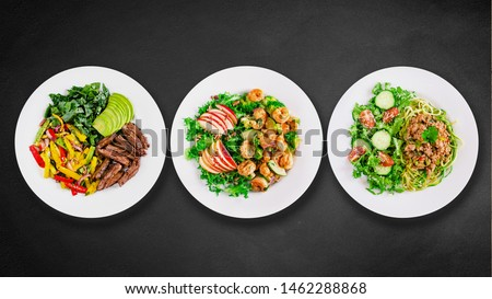 Assortment of various healthy keto paleo meals on white plate. Black stone background. Top view. Isolated. Space for text. Royalty-Free Stock Photo #1462288868