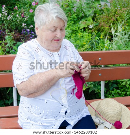 elderly woman knits with knitting sitting on a bench outdoors #1462289102