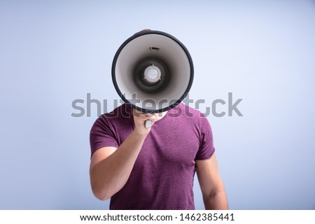 Close-up Of A Beard Man Shouting Through A Megaphone Against Gray Background Royalty-Free Stock Photo #1462385441