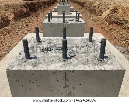 Row of reinforced concrete foundations with metal anchor bolts designed for the installation of metal columns. Foundations of warehouse on the construction site #1462424096
