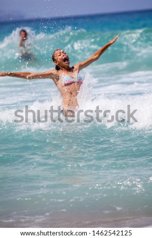 Young girl laughing and crying in the spray of waves at sea on a sunny day #1462542125