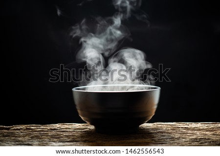 Steam of hot soup with smoke wood bowl on dark background.selective focus.hot food concept #1462556543