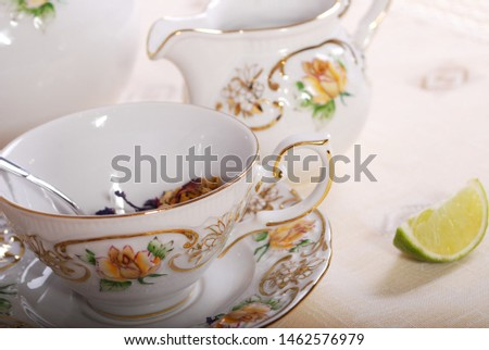 Very elegant tea set of porcelain with a luxury design of tea cups and saucers. Antique decoration with ceramic embossed roses hand painted with gold. Table arrangement with lemon, herbs and flower. #1462576979