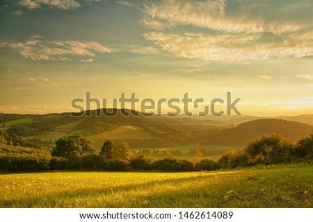 Sunset over hilly landscape, the golden glow of the setting sun, meadow in the foreground #1462614089