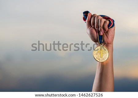 Hand holding gold medal on against cloudy twilight sky background, The winner and successful concept  #1462627526
