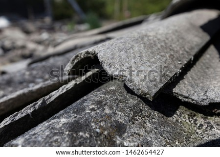 Demolition site with an asbestos issue, close-up view of the broken and fibrous slice of corrugated asbestos cement sheets #1462654427