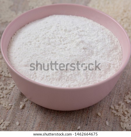Gluten free rice flour in a pink bowl, side view. Closeup. #1462664675