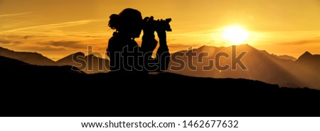 Photographer at sunrise in the mountains Silhouette #1462677632
