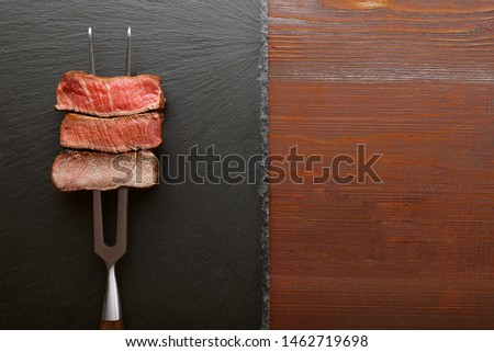 Three pieces of meat on a fork for meat. three types of meat roasting, rare, medium,well done.  #1462719698