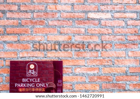 """Bicycle Parking Only"" sign in English and Chinese texts with illustration on acrylic board against orange brick wall."