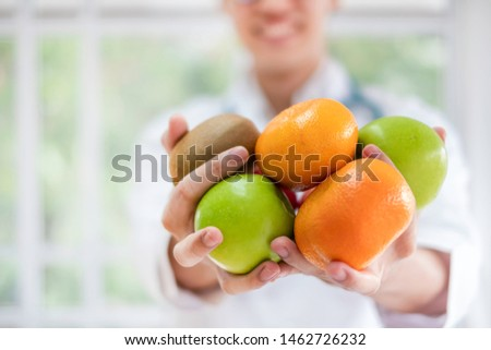 Asian nutritionist in lab coat holding organic fruits by hands in hospital. The food specialist has expertise in considering which nutrition that fit for patients diet & lifestyle. Health concept.   #1462726232
