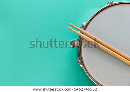 Drum and drum stick on green table background, top view, music concept #1462745552