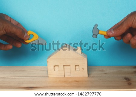 Wooden house and two hands with miniature tools - a hammer and a saw. Concept repair or building a house. #1462797770