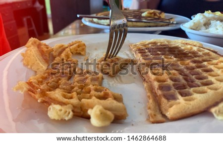 Waffles are covered in syrup on a breakfast table. #1462864688