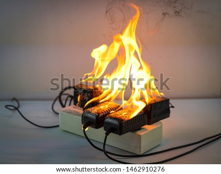 On fire adapter at plug Receptacle on white background, Electric short circuit failure resulting in electricity wire burnt  #1462910276