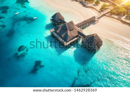 Aerial view of beautiful hotel on the water in ocean at sunset in summer. Zanzibar, Africa. Top view. Landscape with wooden hotel on the sea, azure water, sandy beach, green palm trees. Luxury resort #1462928369