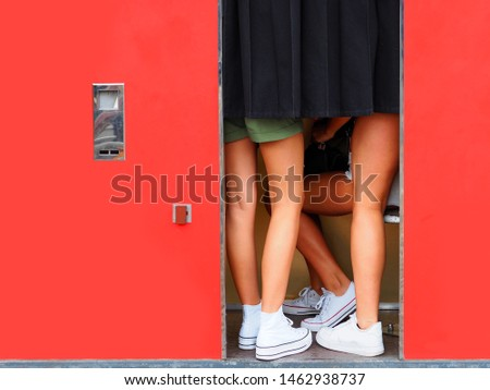 Girls are photographed in a photo booth. Red cabin, womans legs
