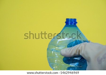blue plastic bottle held in hand with gloves, yellow background #1462946969
