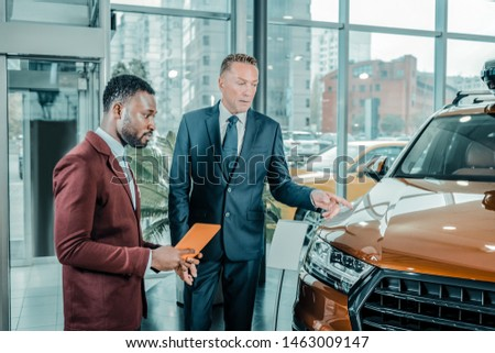 Looking for the best. Serious businessman pointing on the orange automobile choosing a new suitable car in a car showroom. #1463009147