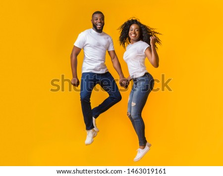 Cheerful Black Man And Woman Are Jumping In The Air, holding hands, copy space #1463019161