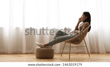 Girl Resting in Armchair and Talking on Phone near Window, Free Space #1463019179