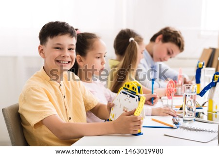 Stem education. Happy boy creating robot at lab, smiling to camera #1463019980
