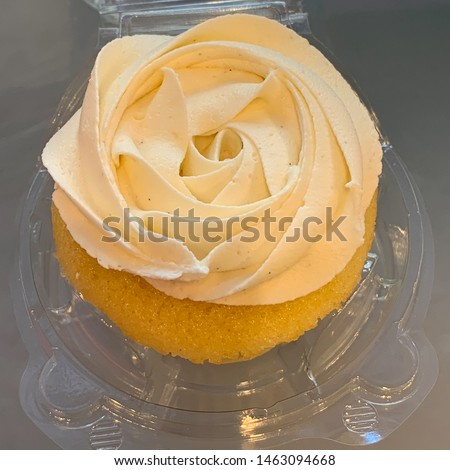 Vanilla cupcake with buttercream frosting on a individual to go container.
