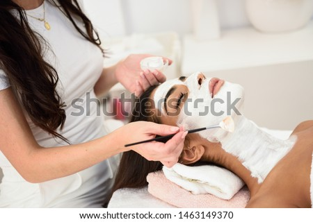 Aesthetics applying a mask to the face of a beautiful woman in modern wellness center. Beauty and Aesthetic concepts. #1463149370