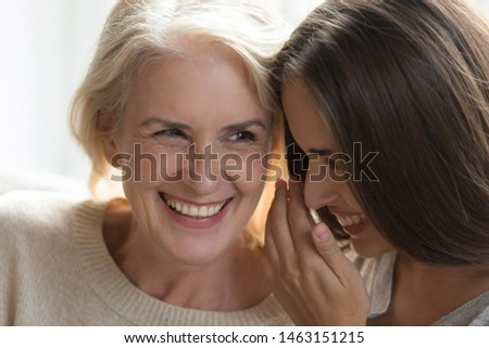 Laughing middle aged mother daughter gossiping sit close to each other spend enjoy time together, grandmother adult granddaughter best friends, intimates trusted person, love devotion, close up image #1463151215