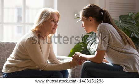 Grown up daughter holding hands of middle aged mother relatives female sitting look at each other having heart-to-heart talk, understanding support care and love of diverse generations women concept #1463151296