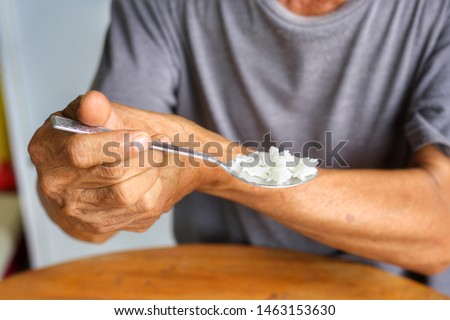 Elderly man is holding his hand while eating because Parkinson's disease.Tremor is most symptom and make a trouble for doing activities such as eat or drink.Health care or elderly concept.Front view. #1463153630
