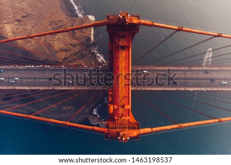 Aerial view of Golden Gate Bridge in foggy visibility during evening time, metropolitan transportation  infrastructure, birds eye view of automotive car vehicles on road of suspension construction  #1463198537