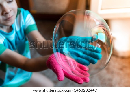 boy playing with a soap bubble. gloves for playing with soap bubbles. big bubble #1463202449