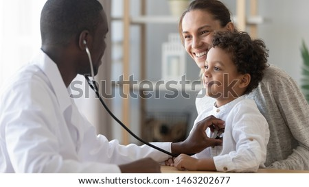 African male pediatrician hold stethoscope exam child boy patient visit doctor with mother, black paediatrician check heart lungs of kid do pediatric checkup in hospital children medical care concept Royalty-Free Stock Photo #1463202677