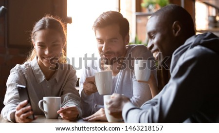 Smiling diverse millennial people meeting in cafe drinking coffee watch funny video on smartphone together, happy multiracial friends gather in coffeeshop have fun using cellphone enjoying beverage