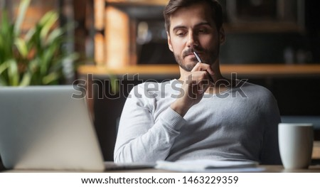 Pensive bearded man sitting at table drink coffee work at laptop thinking of problem solution, thoughtful male employee pondering considering idea looking at computer screen making decision #1463229359