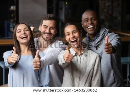 Group picture of overjoyed multiracial young people stand gathering in coffeeshop show thumb up recommending service, portrait of smiling diverse friends posing laughing give good recommendation