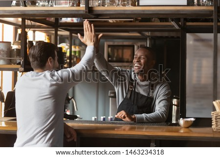 Overjoyed african American barista give high five celebrating successful business cafe option with manager, excited black waiter greeting friend at bar or cafe, join hands having fun with client #1463234318