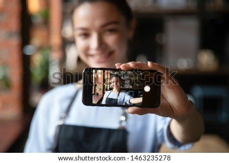 Smiling beautiful young waitress hold smartphone making self-portrait picture on device, happy positive female staff in apron take selfie on cellphone posing for picture in cafe or restaurant