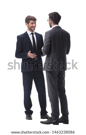 in full growth. two young businessmen discussing something Royalty-Free Stock Photo #1463238086