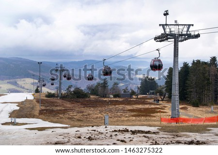 A ski lift with a number of gondolas on a cable for passenger transport in the mountains of holidaymakers with a snow destination in Willingen, Germany #1463275322