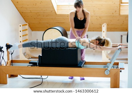 Brunette caucasian woman personal trainer during workout session on pilates reformer bed equipment with female client in medical office or studio. Healthy lifestyle rehabilitation concept.Full hieight #1463300612