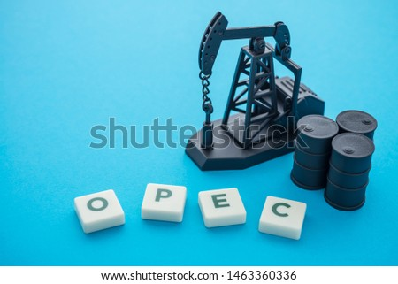 Oil pump jack, barrels and word OPEC Organization of the Petroleum Exporting Countries on blue background. Concept of crude oil production, petroleum industry or petrodollar.