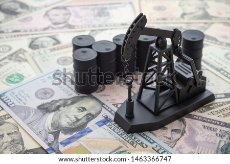 Spending or investment of a country's revenues from petroleum exports industry (Petrodollar). Oil pump jack and barrels on US dollar banknotes. Concept of crude oil production, petroleum industry. #1463366747