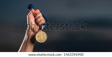 Hand holding gold medal on against cloudy twilight sky background, The winner and successful concept  #1463396900